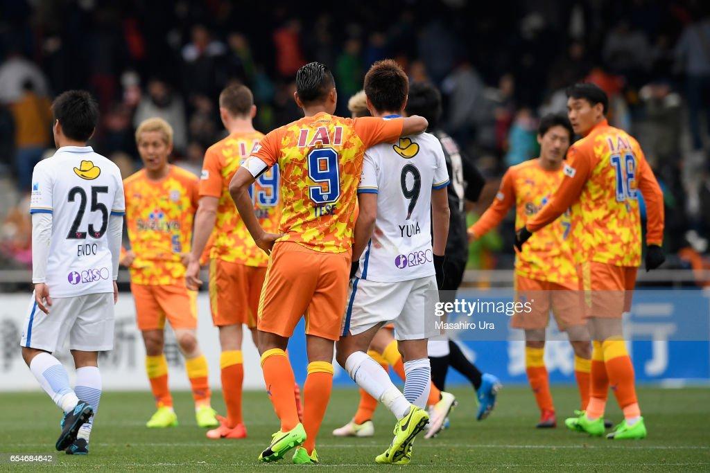 Yuma Suzuki of Kashima Antlers is embraced by Chong Tese of Shimizu S-Pulse after the J.League J1 match between Shimizu S-Pulse and Kashima Antlers at IAI Stadium Nihondaira on March 18, 2017 in Shizuoka, Japan.