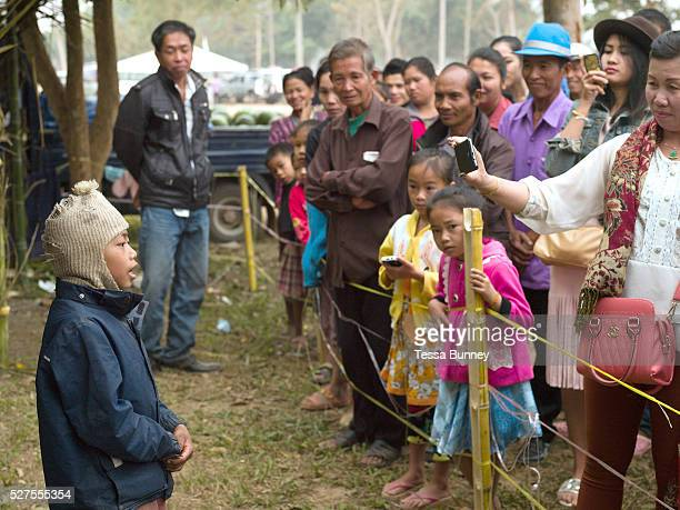 A Yumbri ethnic minority boy sings a song in front of a crowd of Lao tourists at the Sayaboury elephant festival Sayaboury province Lao PDR The...