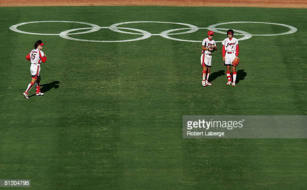 Yumi Iwabuchi of Japan confers with teammate Eri Yamada as teammate Yuki Sato runs over to join them during a break in the softball bronze medal...
