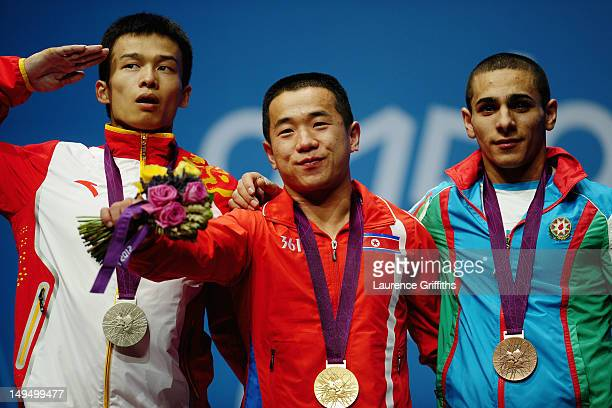 Yun Chol Om of DPR Korea celebrates with the gold medal Jingbiao Wu of China with the silver medal and Valentin Hristov of Azerbaijan with the bronze...