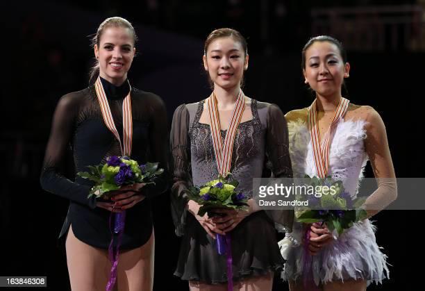 Yuna Kim of South Korea celebrates winning the gold medal with Carolina Kostner of Italy winning silver medal and Mao Asada of Japan winning the...