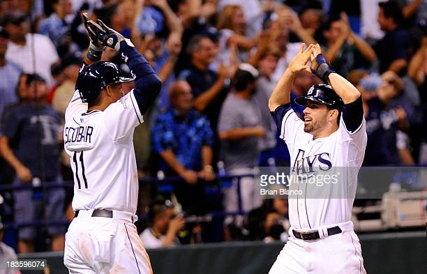 Yunel Escobar and David DeJesus of the Tampa Bay Rays celebrate after scoring on a threerun home run by Evan Longoria in the fifth inning against the...