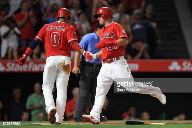Yunel Escobar congratulates Mike Trout after scoring on a double by Albert Pujols of the Los Angeles Angels of Anaheim during the fifth inning of a...