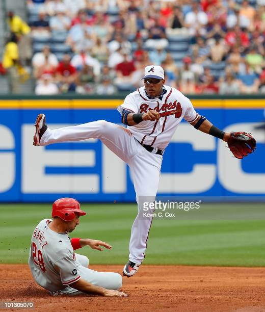 Yunel Escobar of the Atlanta Braves leaps as he turns a double play over Raul Ibanez of the Philadelphia Phillies at Turner Field on May 31 2010 in...