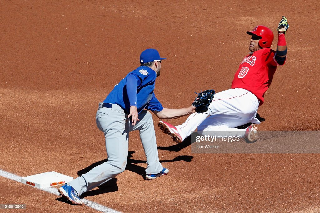 Yunel Escobar #0 of the Los Angeles Angels is tagged out at third by Kris Bryant #17 of the Chicago Cubs in the first inning during the spring training game at Tempe Diablo Stadium on March 6, 2017 in Tempe, Arizona.