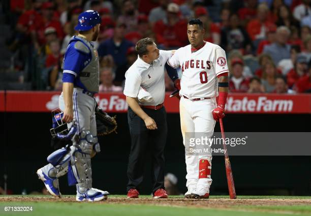 Yunel Escobar of the Los Angeles Angels of Anaheim is attended to by a trainer after being brushed back by a pitch as Russell Martin of the Toronto...