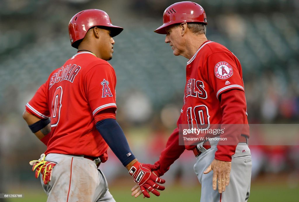 Yunel Escobar #0 of the Los Angeles Angels of Anaheim is congratulated by third base coach Ron Roenicke #10 after Escobar hit a three-run homer against the Oakland Athletics in the top of the second inning at Oakland Alameda Coliseum on May 9, 2017 in Oakland, California.