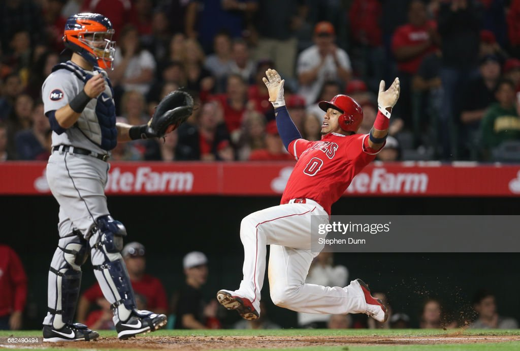 Yunel Escobar #0 of the Los Angeles Angels of Anaheim slides home with a run in the sixth inning past catcher Alex Avila #31 of the Detroit Tigers at Angel Stadium of Anaheim on May 12, 2017 in Anaheim, California.