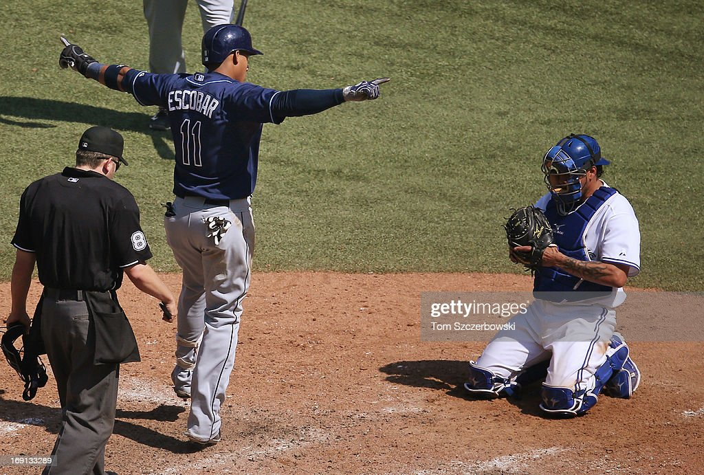 <a gi-track='captionPersonalityLinkClicked' href=/galleries/search?phrase=Yunel+Escobar&family=editorial&specificpeople=757358 ng-click='$event.stopPropagation()'>Yunel Escobar</a> #11 of the Tampa Bay Rays celebrates his two-run home run in the ninth inning by gesturing towards the fans during MLB game action as <a gi-track='captionPersonalityLinkClicked' href=/galleries/search?phrase=Henry+Blanco&family=editorial&specificpeople=211366 ng-click='$event.stopPropagation()'>Henry Blanco</a> #22 of the Toronto Blue Jays looks on on May 20, 2013 at Rogers Centre in Toronto, Ontario, Canada.