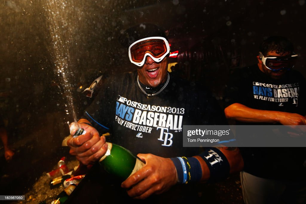 <a gi-track='captionPersonalityLinkClicked' href=/galleries/search?phrase=Yunel+Escobar&family=editorial&specificpeople=757358 ng-click='$event.stopPropagation()'>Yunel Escobar</a> #11 of the Tampa Bay Rays celebrates their 5 to 2 win over the Texas Rangers in the locker room after the American League Wild Card tiebreaker game at Rangers Ballpark in Arlington on September 30, 2013 in Arlington, Texas.
