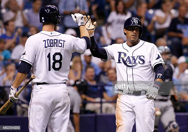 Yunel Escobar of the Tampa Bay Rays celebrates with Ben Zobrist of the Tampa Bay Rays after scoring off of a wild pitch by Tom Wilhelmsen of the...