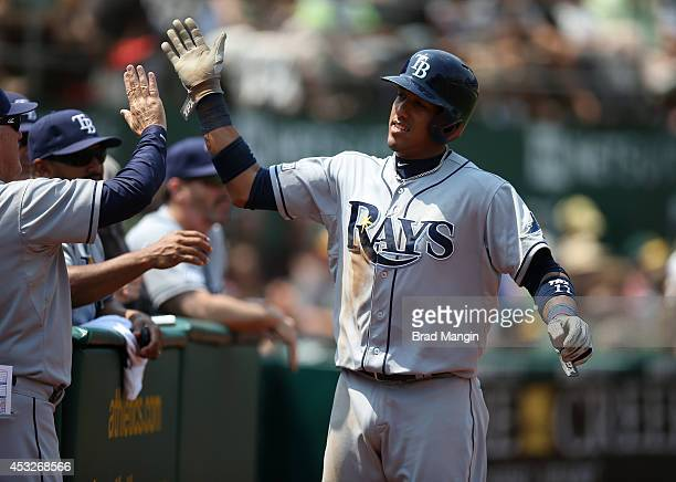 Yunel Escobar of the Tampa Bay Rays celebrates with his teammates after scoring a run against the Oakland Athletics during the game at Oco Coliseum...
