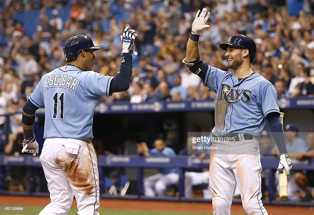 Yunel Escobar of the Tampa Bay Rays celebrates with teammate Kevin Kiermaier after scoring from second base off of a single by Logan Forsythe during...
