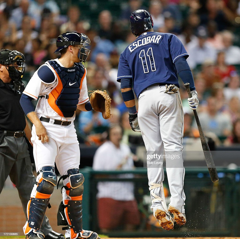 Yunel Escobar #11 of the Tampa Bay Rays reacts after being called out on strikes looking by home plate umpire John Hirschbeck in the third inning as Jason Castro #15 of the Houston Astros looks on at Minute Maid Park on July 1, 2013 in Houston, Texas.