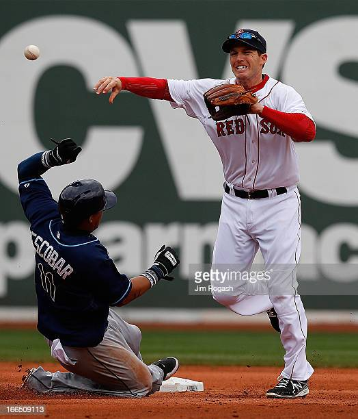 Yunel Escobar of the Tampa Bay Rays slides as Stephen Drew of the Boston Red Sox turns a double play in the seventh inning at Fenway Park on April 13...