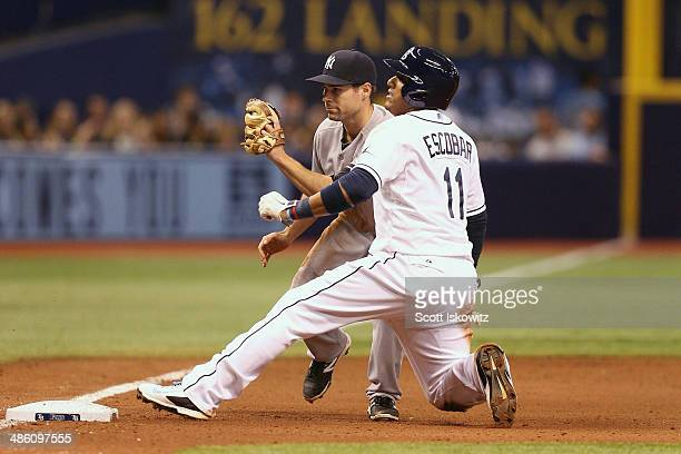 Yunel Escobar of the Tampa Bay Rays slides safely into third against Scott Sizemore of the New York Yankees at Tropicana Field on April 18 2014 in St...