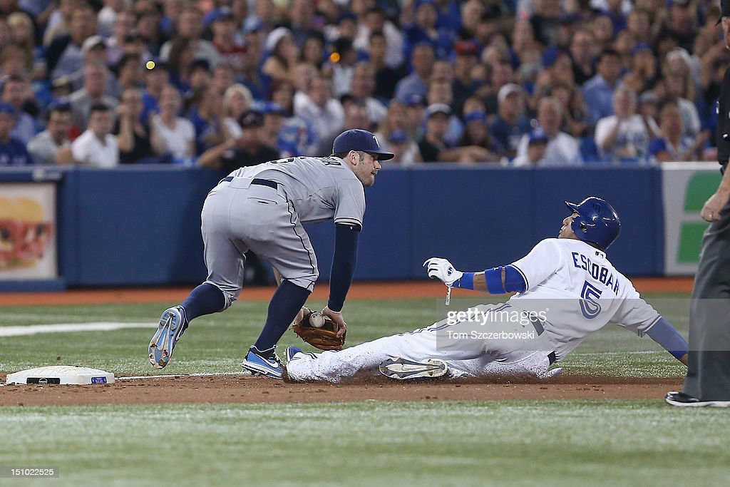 <a gi-track='captionPersonalityLinkClicked' href=/galleries/search?phrase=Yunel+Escobar&family=editorial&specificpeople=757358 ng-click='$event.stopPropagation()'>Yunel Escobar</a> #5 of the Toronto Blue Jays advances to third base in the third inning during MLB game action as <a gi-track='captionPersonalityLinkClicked' href=/galleries/search?phrase=Evan+Longoria&family=editorial&specificpeople=2349329 ng-click='$event.stopPropagation()'>Evan Longoria</a> #3 of the Tampa Bay Rays handles the throw on August 30, 2012 at Rogers Centre in Toronto, Ontario, Canada.
