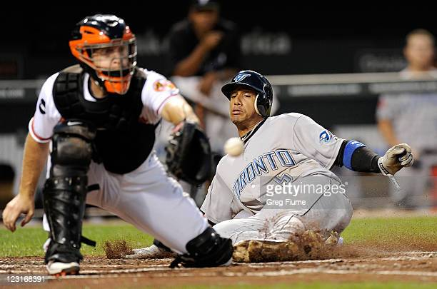 Yunel Escobar of the Toronto Blue Jays slides into home plate ahead of the throw to catcher Craig Tatum of the Baltimore Orioles in the third inning...