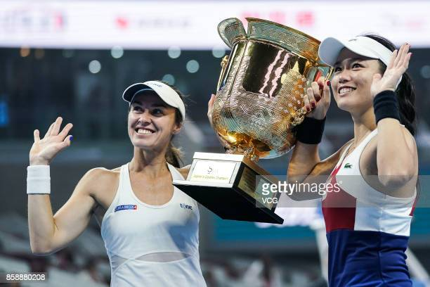 YungJan Chan of Chinese Taipei and Martina Hingis of Switzerland pose with the trophy after winning the Women's doubles final match against Timea...