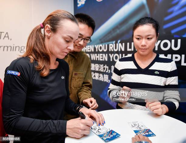 YungJan Chan of Chinese Taipei and Martina Hingis of Switzerland sign autographs after winning the Women's Doubles Final against Timea Babos of...