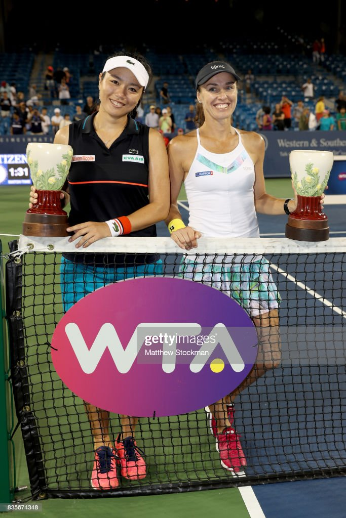 Yung-Jan Chan of Taipei and Martina Hingis of Switzerland pose for photographers with the winner's trophy after defeating Su-Wei Hsieh of Taipei and Monica Niculescu of Romania in the women's double final during day 8 of the Western & Southern Open at the Lindner Family Tennis Center on August 19, 2017 in Mason, Ohio.
