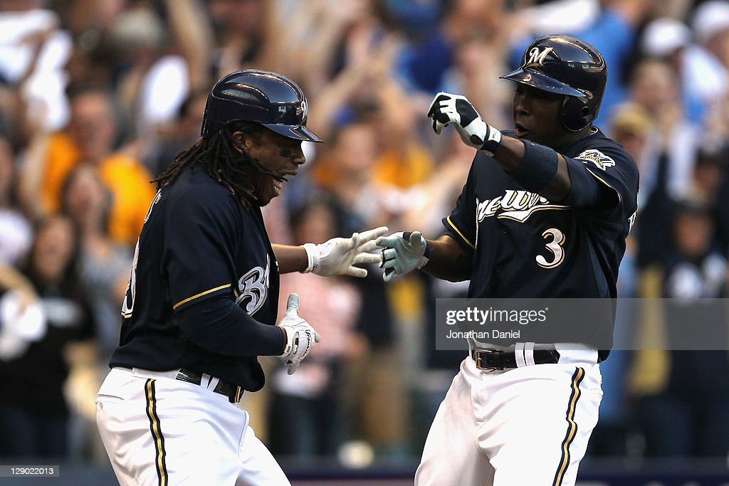 Yuniesky Betancourt and Rickie Weeks of the Milwaukee Brewers celebrate after they scored on a 2run home run by Betancourt in the during Game one of...