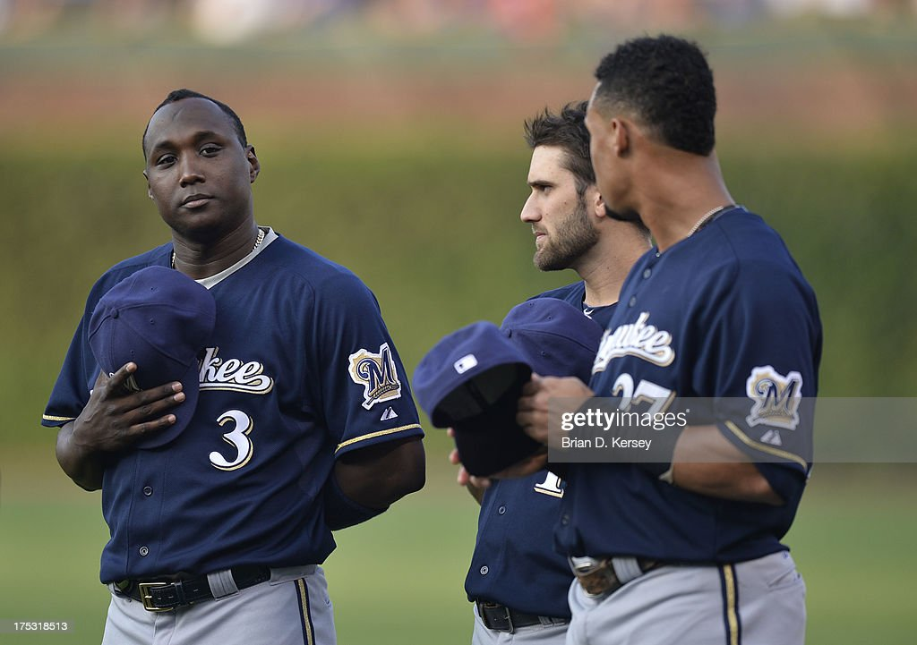 Yuniesky Betancourt Jeff Bianchi and Carlos Gomez of the Milwaukee Brewers stand on the field during the singing of 'The Star Spangled Banner' before...