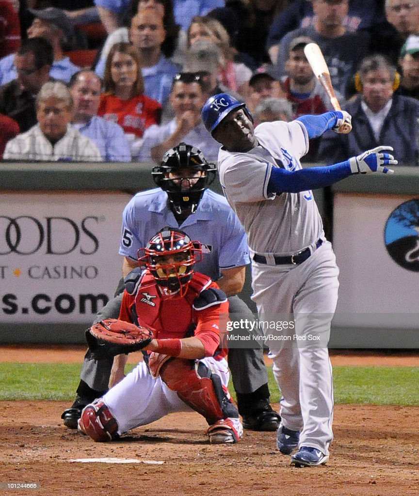 Yuniesky Betancourt of the Kansas City Royals follows through on a grand slam against the Boston Red Sox in front of Victor Martinez and home plate...