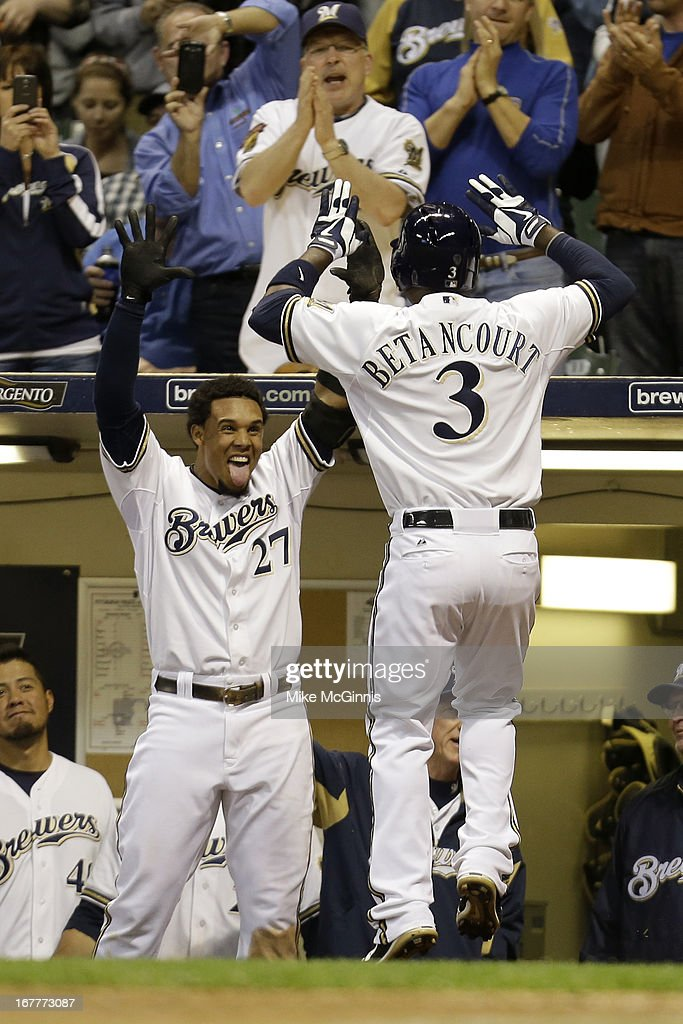 Yuniesky Betancourt of the Milwaukee Brewers celebrates with Carlos Gomez outside the dugout after hitting a solo home run in the bottom of the sixth...