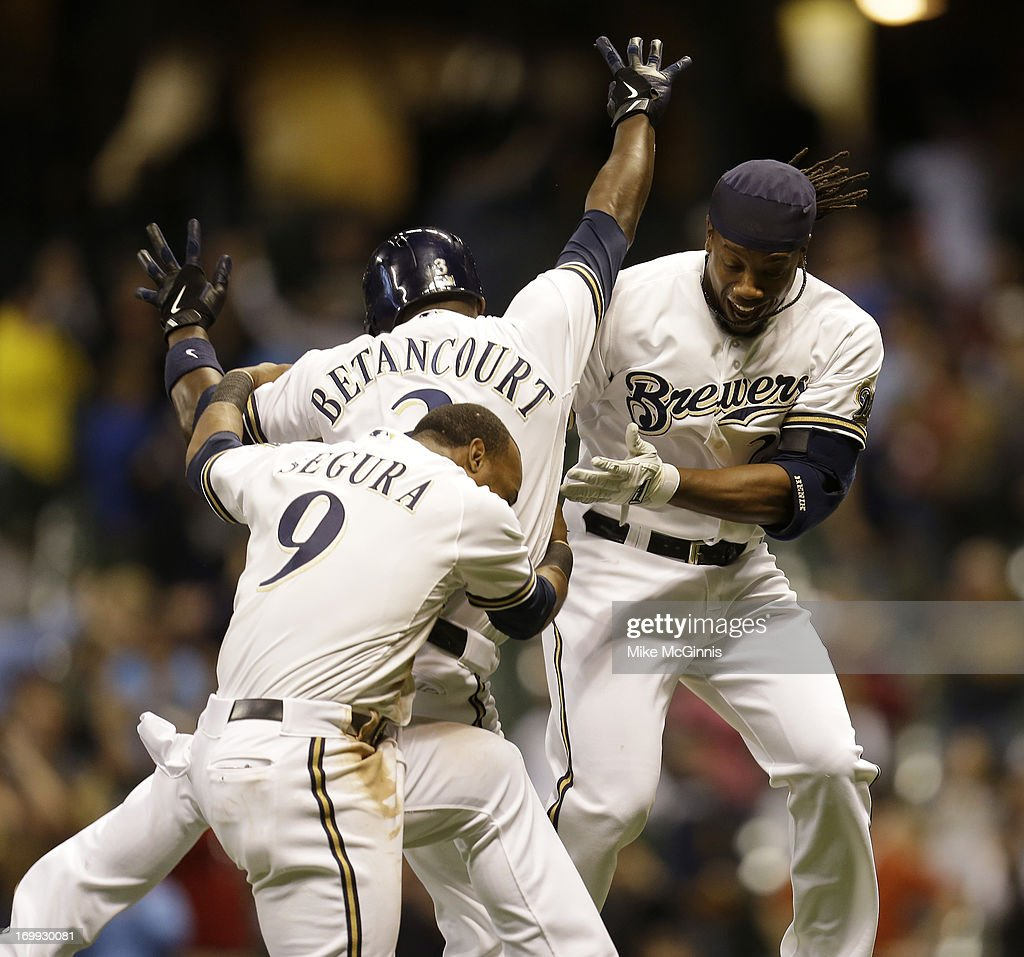 Yuniesky Betancourt of the Milwaukee Brewers celebrates with Rickie Weeks and Jean Segura after hitting a walk off double in the bottom of the tenth...