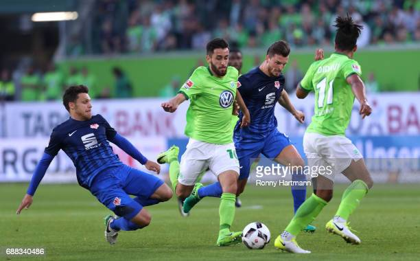 Yunus Malli of Wolfsburg is attacked by Mirko Boland and Gustav Valsvik of Braunschweig the Bundesliga Playoff first leg match between VfL Wolfsburg...