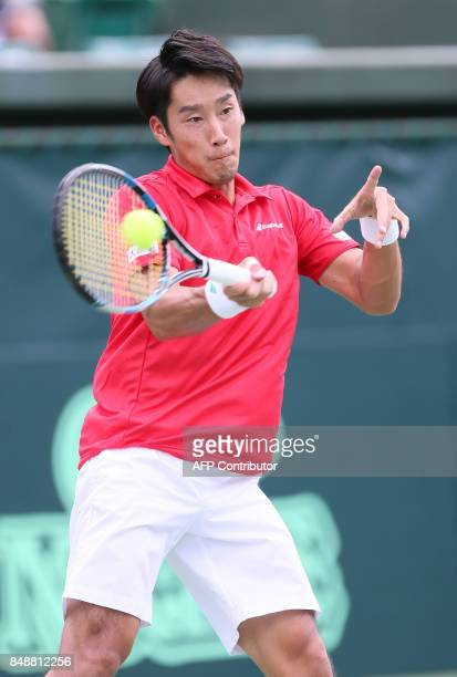 Yuoichi Sugita of Japan hits a return to Thaigo Monteiro of Brazil during the Davis Cup World Group playoff between Japan and Brazil in Osaka western...