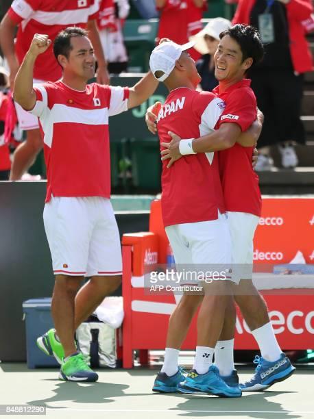 Yuoichi Sugita of Japan hugs head coach Atoshi Iwabuchi after defeating Thiago Monteiro of Brazil during the Davis Cup World Group playoff between...