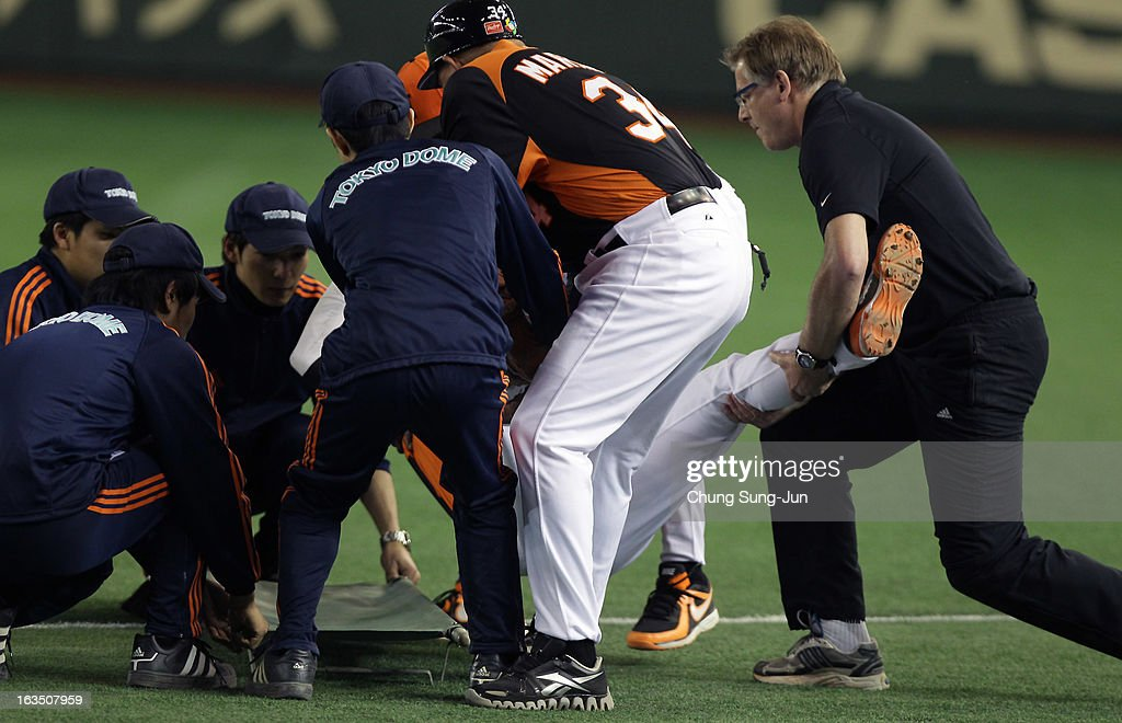 Yurendell de Caster # 22 of Netherlands is placed on a stretcher after he was injured rounding into first base in the sixth inning during the World Baseball Classic Second Round Pool 1 game between Cuba and the Netherlands at Tokyo Dome on March 11, 2013 in Tokyo, Japan.