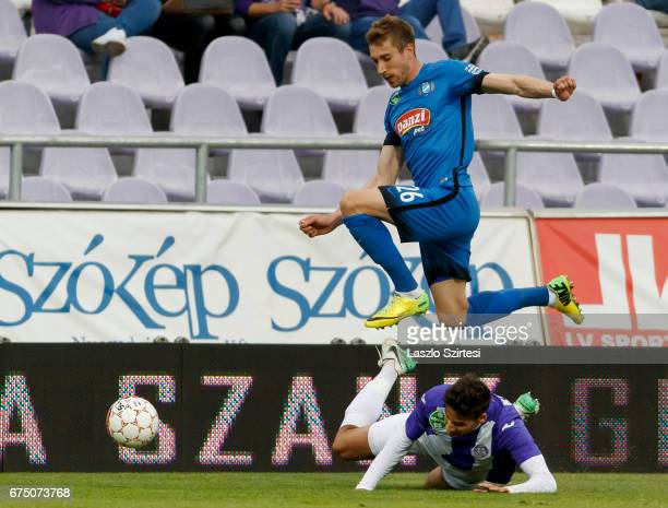 Yuri Kolomoets of MTK Budapest jumps over Akos Kecskes of Ujpest FC during the Hungarian OTP Bank Liga match between Ujpest FC and MTK Budapest at...