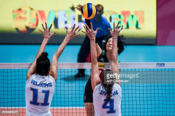 Yurie Nabeya of Japan hits the ball while Stefana Veljkovic and Bojana Zivkovic of Serbia try to block during their match at the Women's Volleyball...