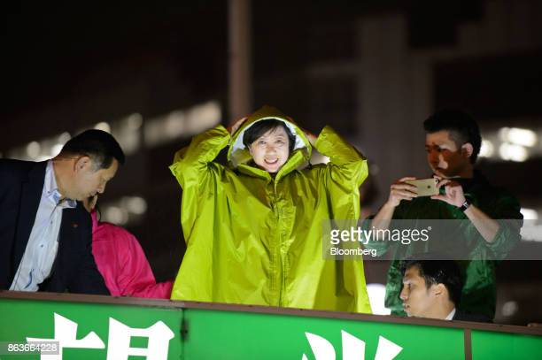 Yuriko Koike governor of Tokyo and leader of the Party of Hope center adjusts her raincoat during an election campaign rally in Tokyo Japan on Friday...