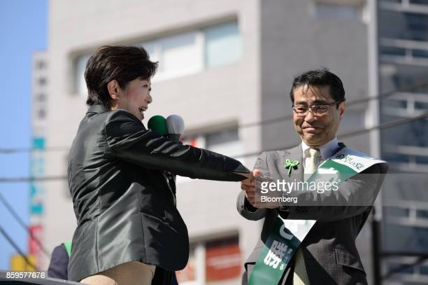 Yuriko Koike governor of Tokyo and leader of the Party of Hope left and Masaru Wakasa a member of the House of Representatives shake hands at an...