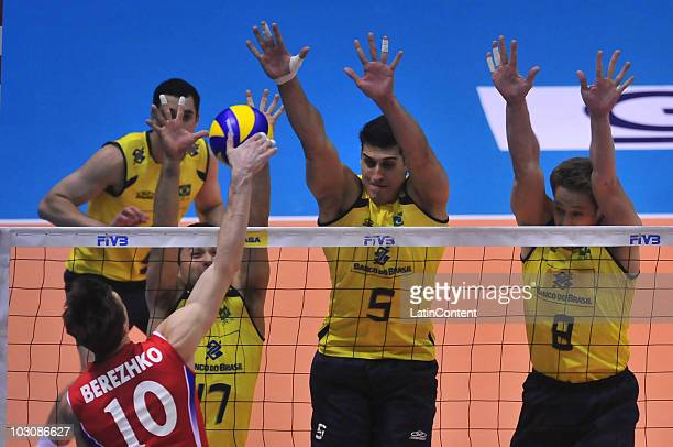 Yury Berezhko of Russia spikes against the block of Marlon Muragati Yared Sidnei dos Santos and Murillo Endres during the final match of FIVB World...