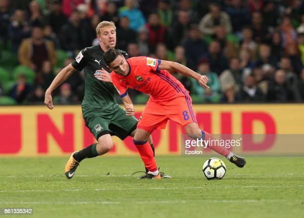 Yury Gazinsky of FC Krasnodar is challenged by Georgi Milanov of FC CSKA Moscow during the Russian Premier League match between FC Krasnodar v FC...