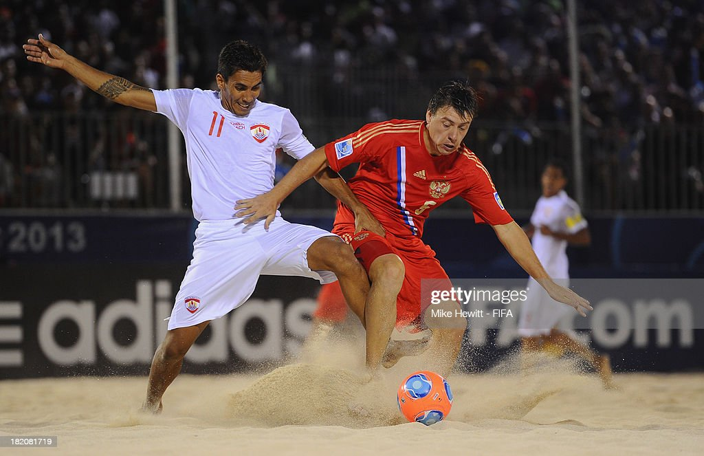 Yury Krasheninnikov of Russia is fouled by Teva Zaveroni of Tahiti during the FIFA Beach Soccer World Cup Tahiti 2013 Semi Final match between Russia and Tahiti at the Tahua To'ata Stadium on September 27, 2013 in Papeete, French Polynesia.