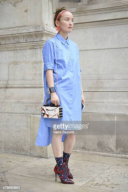 Yusa Wu poses wearing a Peace Bird dress and Tonya Hawkes bag before the Alexis Mabille presentation at the Opera Garnier on July 8 2015 in Paris...
