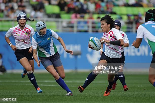 Yusaku Kuwazuru of Japan competes with Umida Saribaeva of Uzbekistan in the Women's Preliminary Round Group A during day eleven of the 2014 Asian...