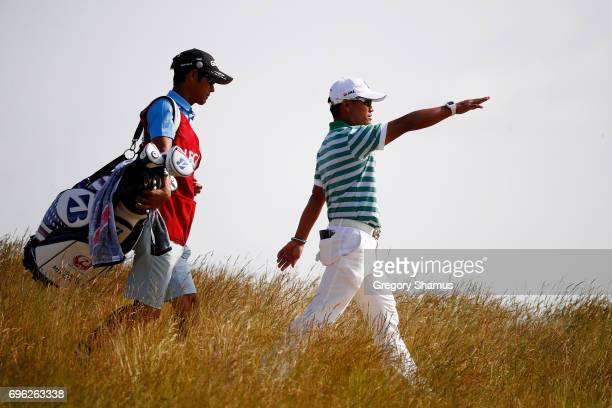 Yusaku Miyazato of Japan and caddy Kunihito Aoyama walks off the sixth hole during the first round of the 2017 US Open at Erin Hills on June 15 2017...