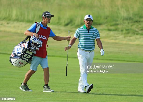 Yusaku Miyazato of Japan hands his club to caddy Kunihito Aoyama walk walking across the fourth hole during the first round of the 2017 US Open at...
