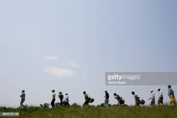 Yusaku Miyazato of Japan Shugo Imahira of Japan and Si Woo Kim of South Korea walk during a practice round prior to the 2017 US Open at Erin Hills on...