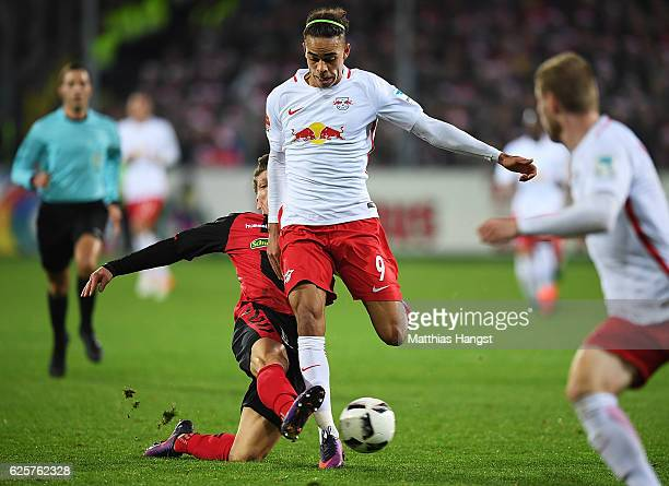 Yussuf Poulsen of RB Leipzig is tackled by Pascal Stenzel of SC Freiburg during the Bundesliga match between SC Freiburg and RB Leipzig at...