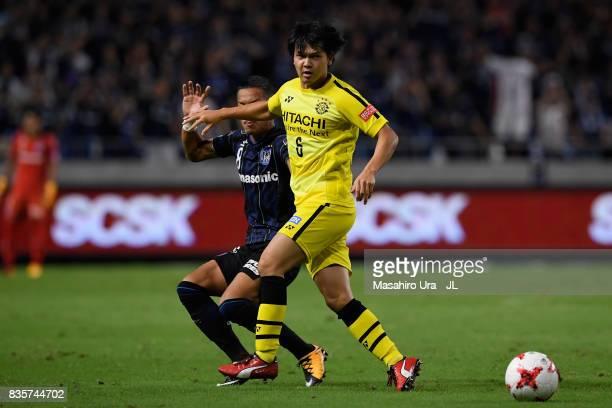 Yusuke Kobayashi of Kashiwa Reysol controls the ball under pressure of Yosuke Ideguchi of Gamba Osaka during the JLeague J1 match between Gamba Osaka...
