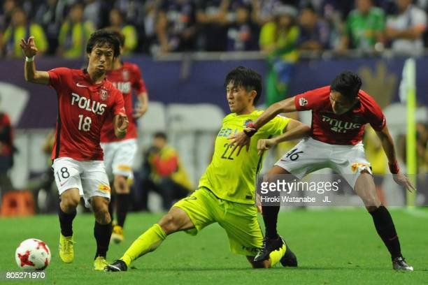 Yusuke Minagawa of Sanfrecce Hiroshima controls the ball under pressure of Yoshiaki Komai and Ryota Moriwaki of Urawa Red Diamonds during the JLeague...