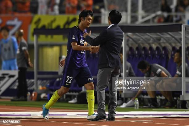 Yusuke Minagawa of Sanfrecce Hiroshima shakes hands with head coach Hajime Moriyasu after substituted during the JLeague J1 match between Sanfrecce...